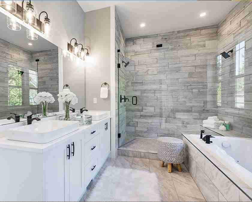 Modern white bathroom with marble shower tiles and glass shower door