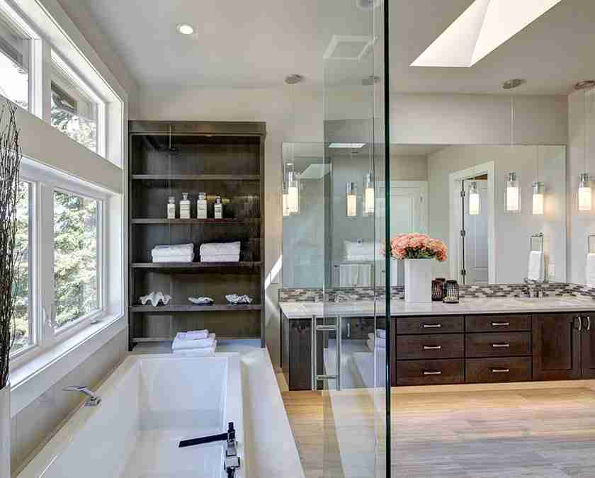 Modern bathroom with large bathtub with glass wall, large window, wooden cabinets, double sinks, and large mirror.