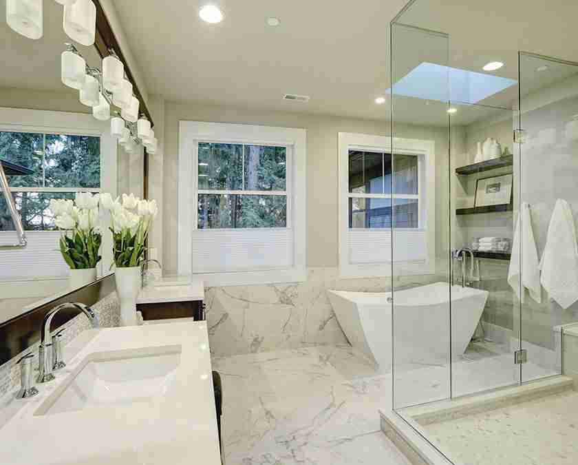 Modern bathroom with squared bathtub, double sinks, two large mirrors, marble flooring, and glass tower shower.