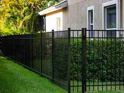 Small house with green lawn, green shrubs, and black painted steel bars fence.